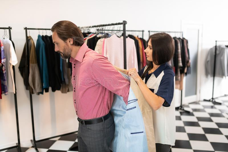 Kind consultant assisting a customer during trying on a blazer. stock photo