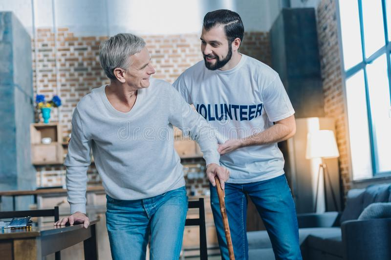 Kind content man helping an aged man stock image