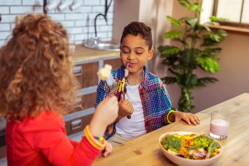 Kind curly-haired girl looking at her friend. Playful mood. Delighted brunette boy expressing positivity while eating vegetables royalty free stock images