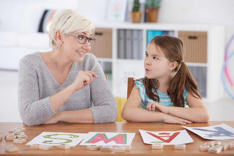Kind, das Alphabet mit Lehrer studiert stockbilder