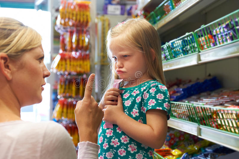 Kind, das Argument mit Mutter am Süßigkeits-Zähler hat stockfoto