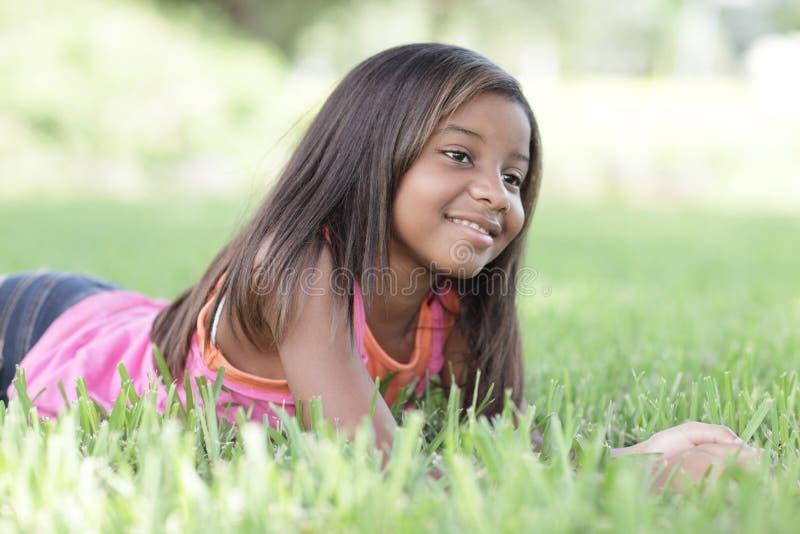 Kind, das auf das Gras legt lizenzfreies stockfoto