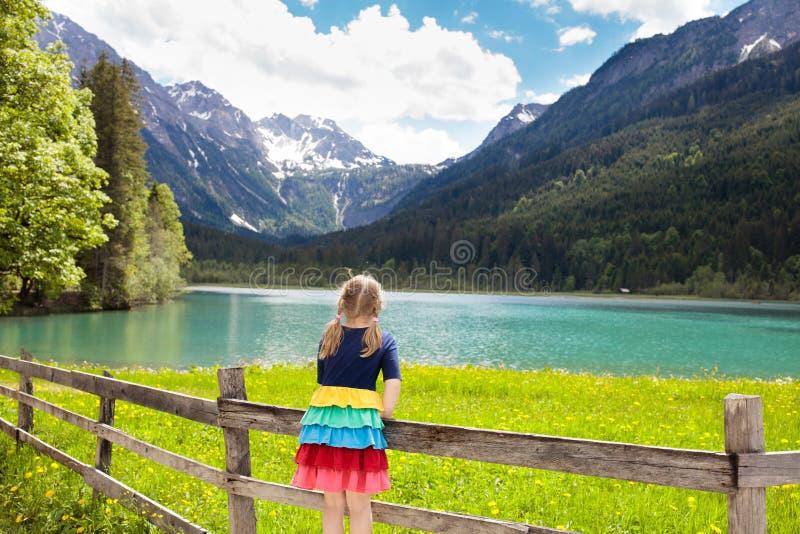 Kind, das auf dem Blumengebiet am Gebirgssee wandert stockfotos