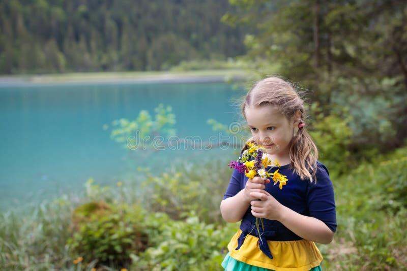 Kind, das auf dem Blumengebiet am Gebirgssee wandert lizenzfreie stockfotos