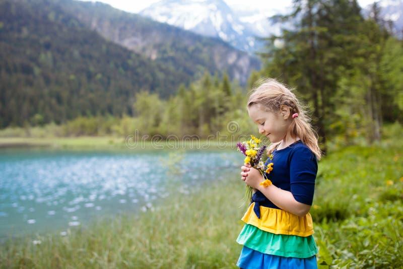 Kind, das auf dem Blumengebiet am Gebirgssee wandert lizenzfreies stockbild