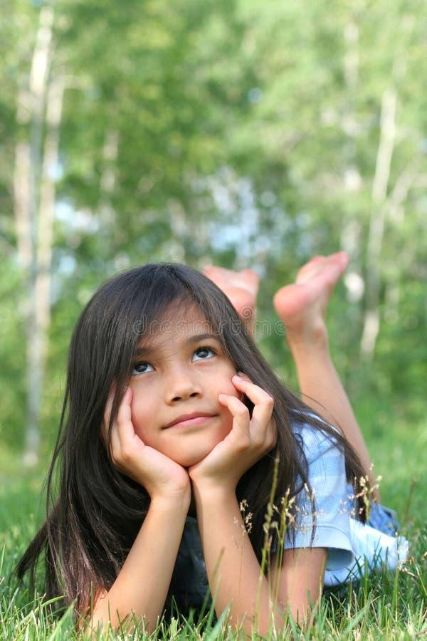 Kind, das auf dem Grasdenken liegt lizenzfreie stockfotos