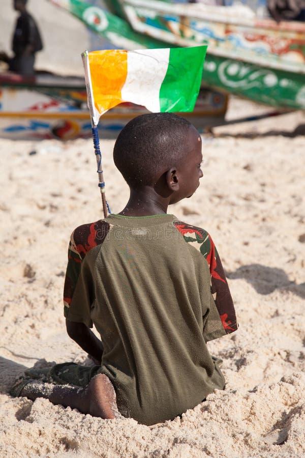 Kind, das auf dem Strand des Saint Louis spielt stockbild