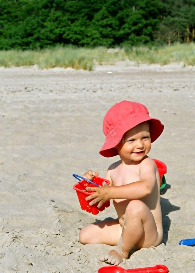 Kind, das auf dem Strand spielt lizenzfreie stockbilder