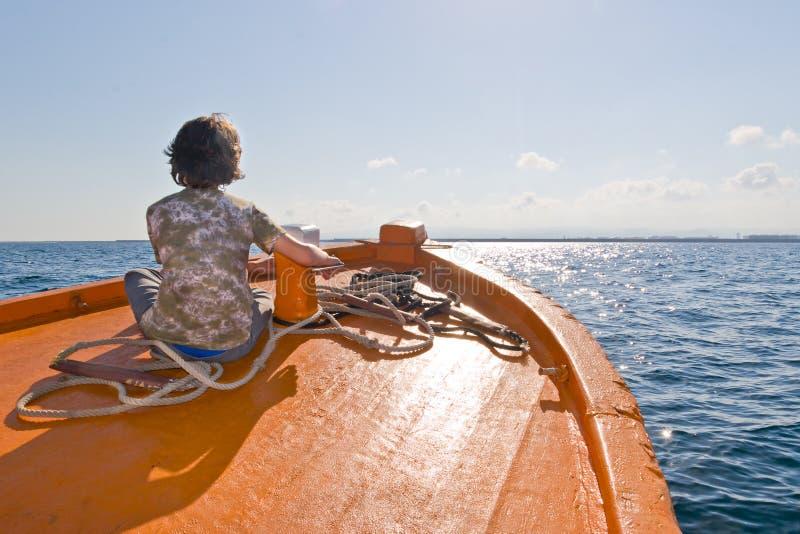 Kind, das auf einem Boot sitzt stockbild