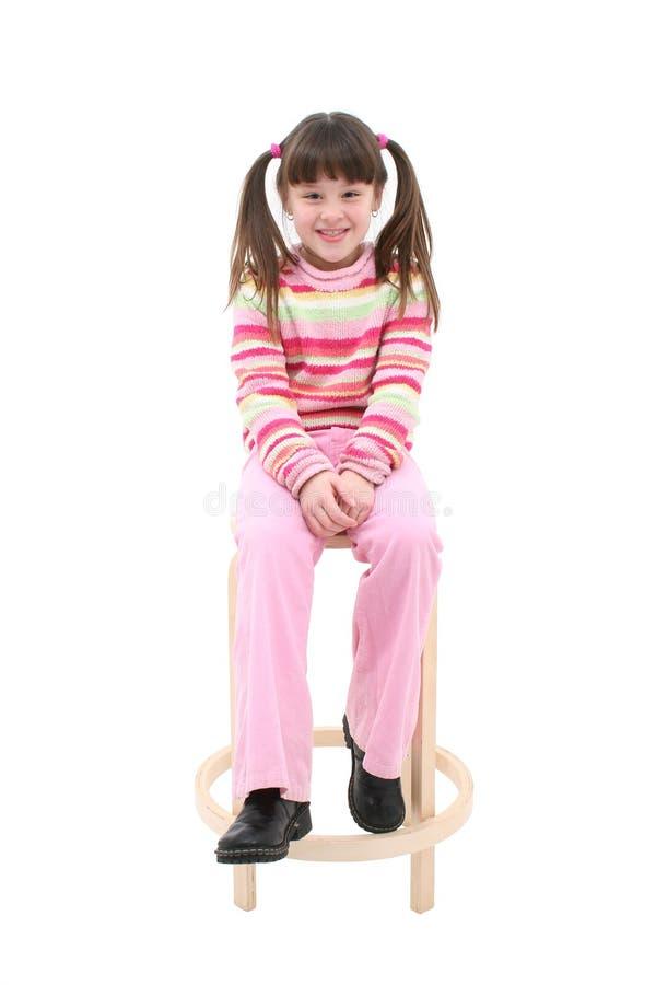 Kind, das auf einem hölzernen Schemel sitzt lizenzfreies stockfoto