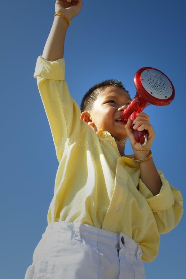 Kind, das auf einem Lautsprecher spricht stockfotografie