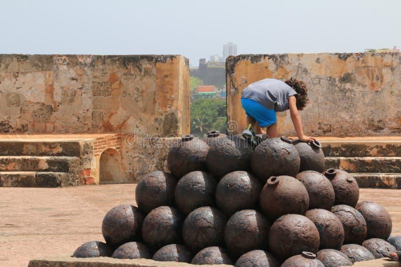 Kind, das auf einem Stapel auf Kanonenkugeln klettert lizenzfreie stockbilder