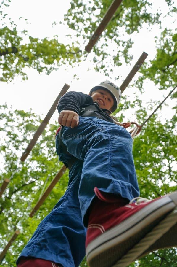 Kind, das auf einen Draht im Erlebnispark geht lizenzfreie stockbilder