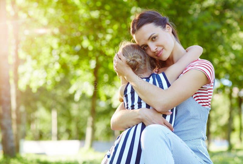 Kind, das auf Mutterhänden sitzt stockbild