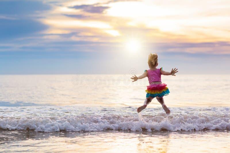 Kind, das auf Ozeanstrand spielt Kind in Sonnenuntergangmeer stockfotos