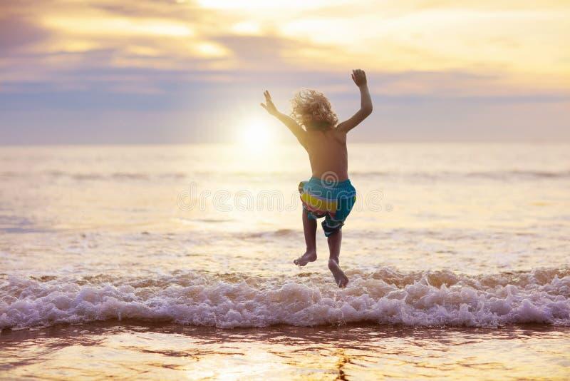Kind, das auf Ozeanstrand spielt Kind in Sonnenuntergangmeer stockfotografie