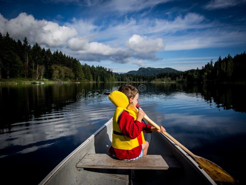 Kind, das auf See canoeing ist stockfoto