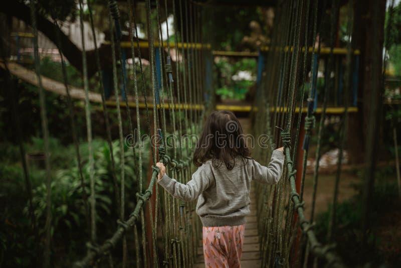 Kind, das auf Spielplatz im Freien in hängender Brücke der Naturüberfahrt spielt lizenzfreies stockfoto