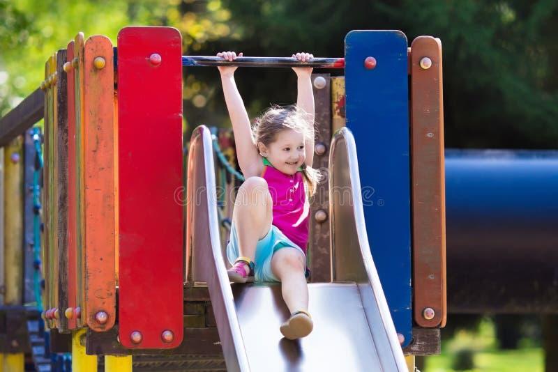 Kind, das auf Spielplatz im Freien im Sommer spielt stockfoto