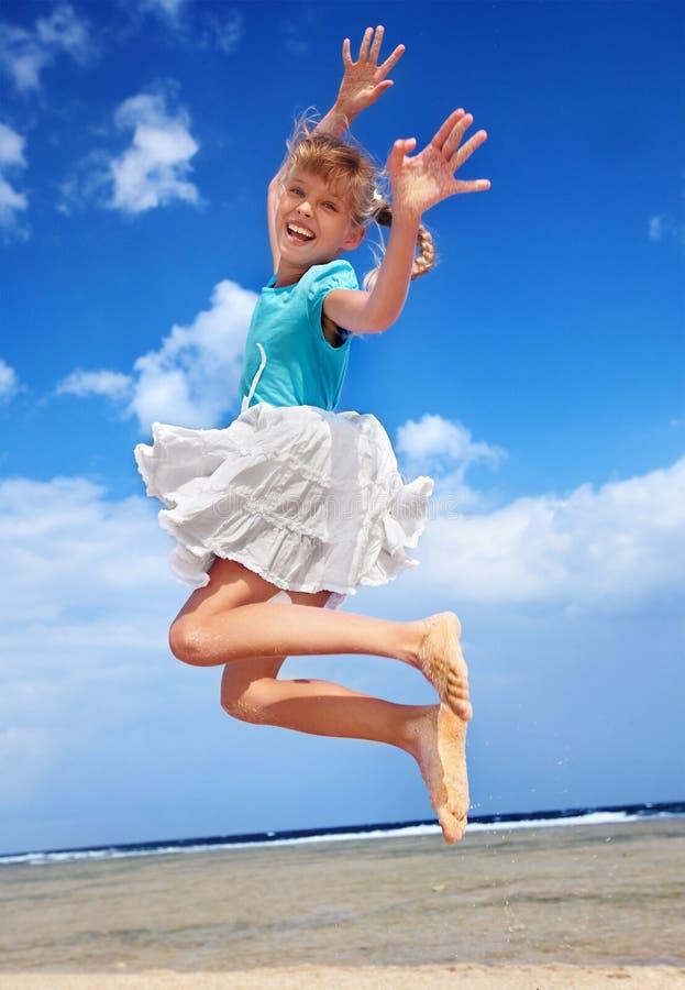 Kind, das auf Strand aganiist blauem Himmel spielt. stockbild