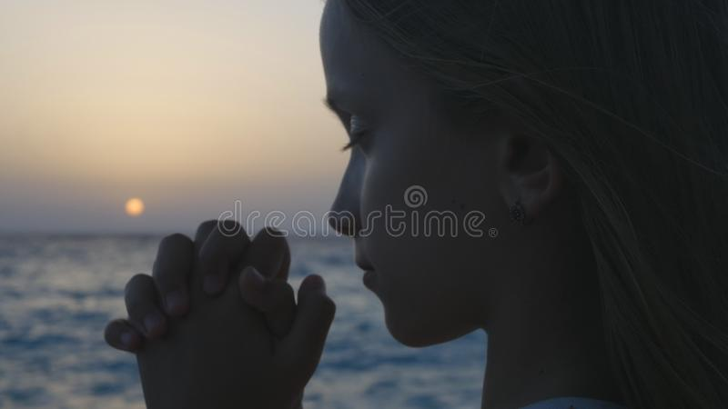 Kind, das auf Strand bei Sonnenuntergang, durchdachtes Gebets-Kind, nachdenkliches Mädchen auf Küste betet stockfoto