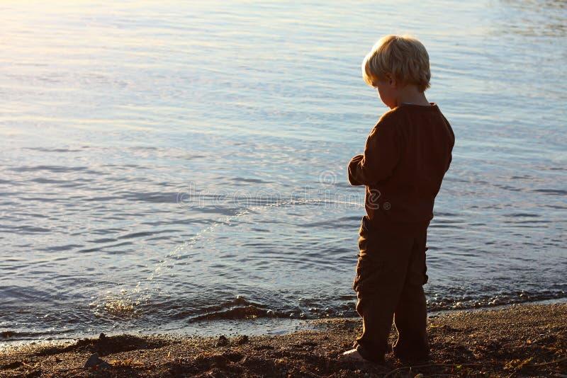 Kind, das auf Strand pinkelt lizenzfreie stockbilder