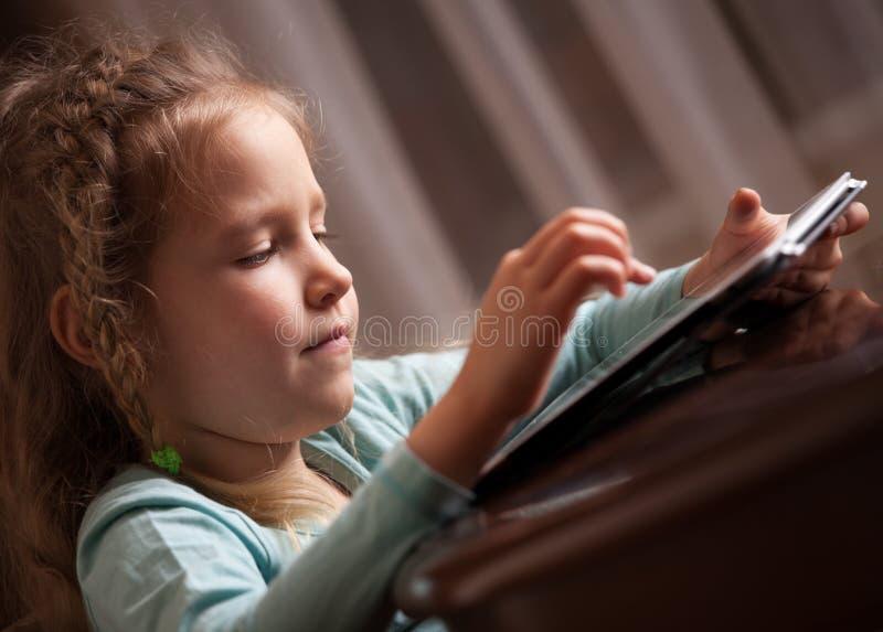Kind, das auf Tablette spielt lizenzfreie stockfotos