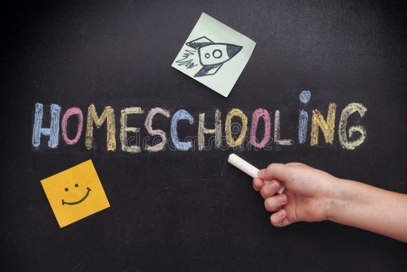 Kind, das auf Wort Homeschooling auf einer Tafel zeigt stockfotografie