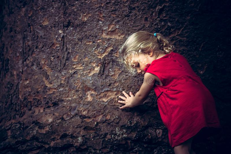 Kind, das Baumstamm-Konzeptabwehrbäume und Klimaerhaltung in der dunklen Weinleseart berührt stockfotos