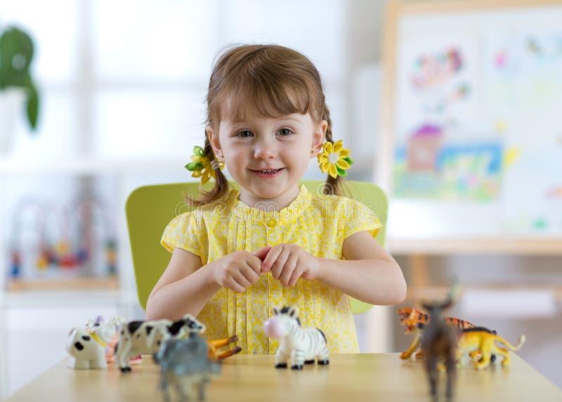 Kind, das bei Tisch mit Tierspielwaren im Kindergarten oder im Haus spielt stockfoto