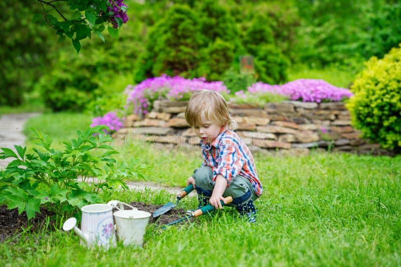 Kind, das Blumen im Garten pflanzt lizenzfreies stockfoto