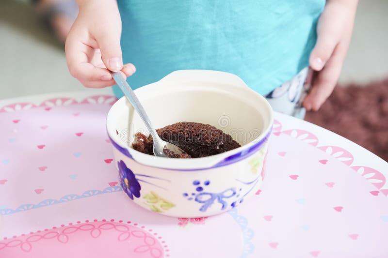 Kind, das Bonbonpuddingwüsten-Schokoladenkuchen-Jungenmädchen mit Löffel und den Teller ungesund isst lizenzfreies stockfoto