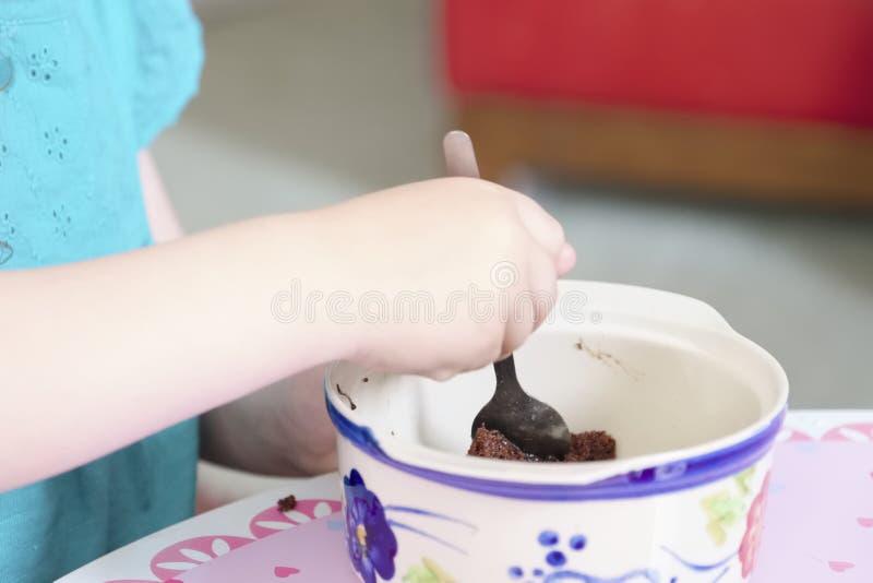Kind, das Bonbonpuddingwüsten-Schokoladenkuchen-Jungenmädchen mit Löffel und den Teller ungesund isst stockbild