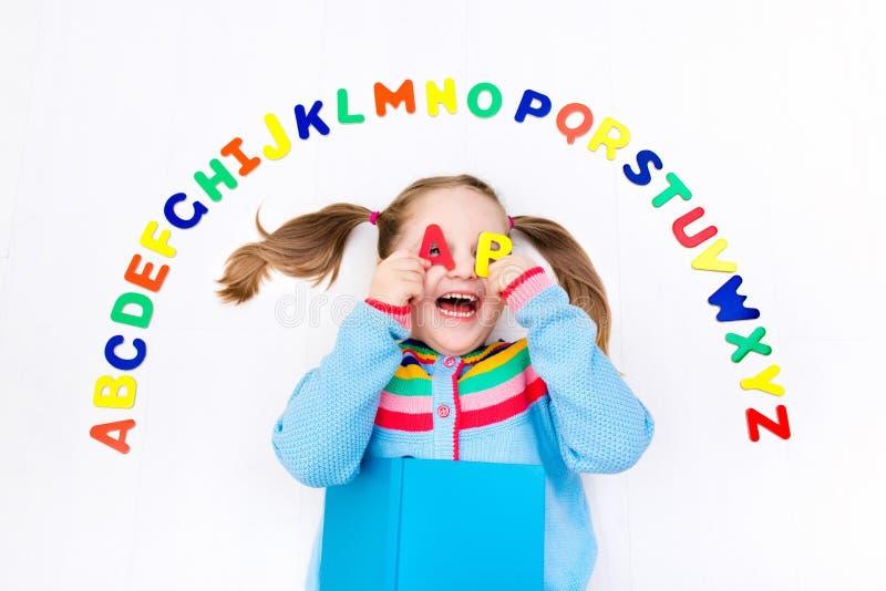 Kind, das Buchstaben des Alphabetes und des Ablesens lernt stockfotografie