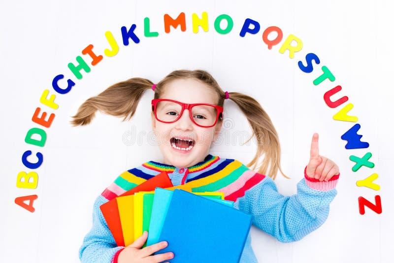 Kind, das Buchstaben des Alphabetes und des Ablesens lernt lizenzfreie stockbilder