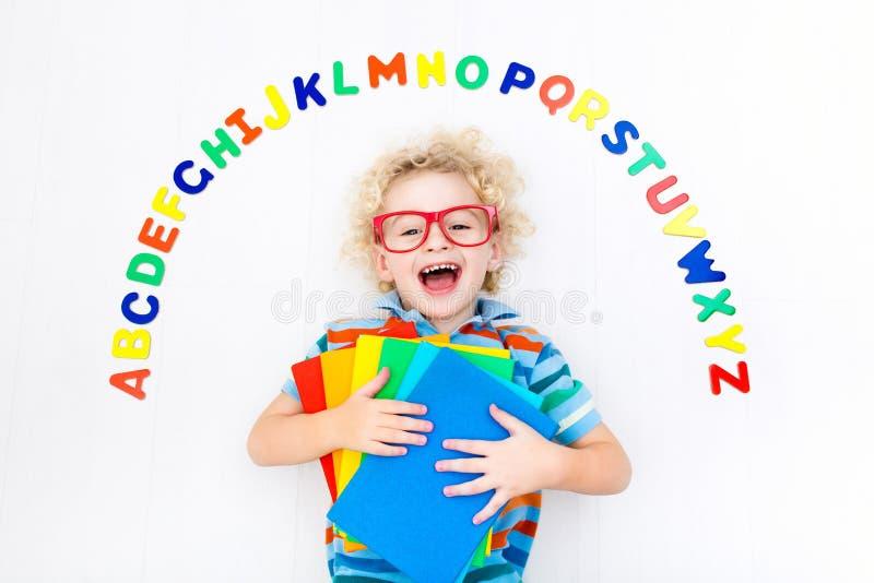 Kind, das Buchstaben des Alphabetes und des Ablesens lernt stockbild