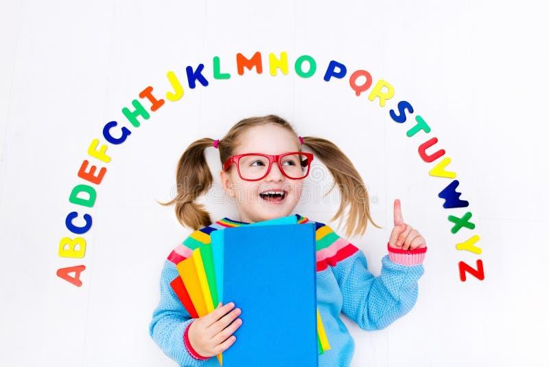Kind, das Buchstaben des Alphabetes und des Ablesens lernt lizenzfreie stockfotografie