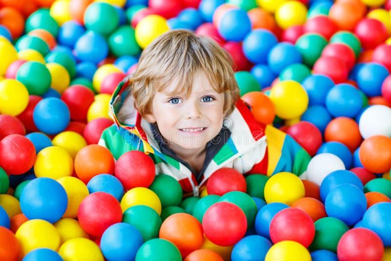 Kind, das am bunten Plastikballspielplatz spielt stockfotos
