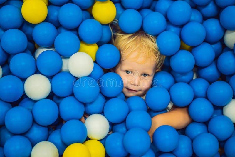 Kind, das in der Ballgrube spielt Bunte Spielwaren f?r Kinder Kindergarten oder Vorschule- Spielraum Kleinkindkind an der Tagesbe lizenzfreie stockbilder