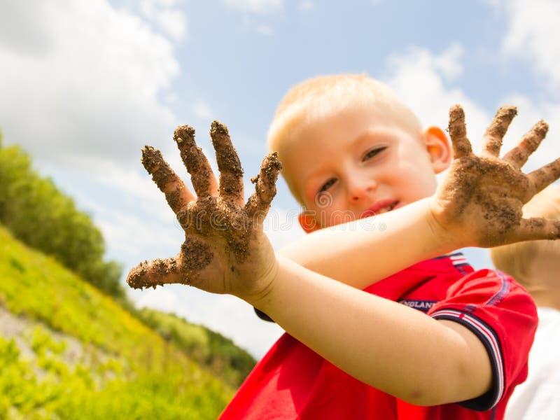 Kind, das der im Freien schmutzige schlammige Hände Vertretung spielt stockfoto