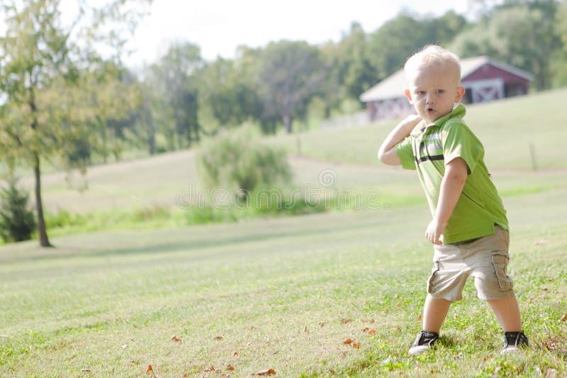 Kind, das draußen einen Ball wirft stockbild