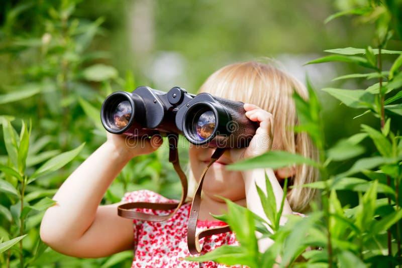 Kind, das durch Binokel schaut lizenzfreies stockbild