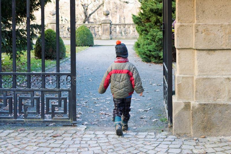 Kind, das durch ein Tor in einen Park oder in einen Garten geht lizenzfreies stockbild