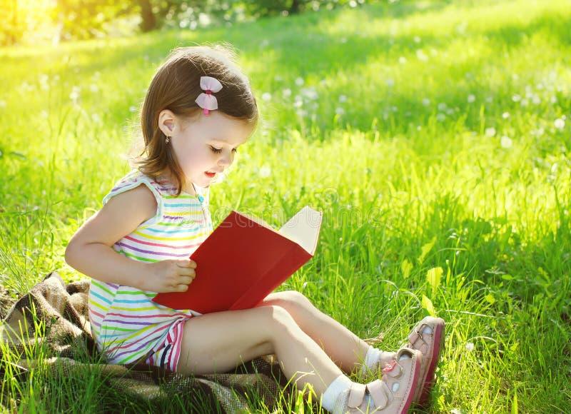 Kind, das ein Buch auf dem Gras im sonnigen Sommer liest stockbilder