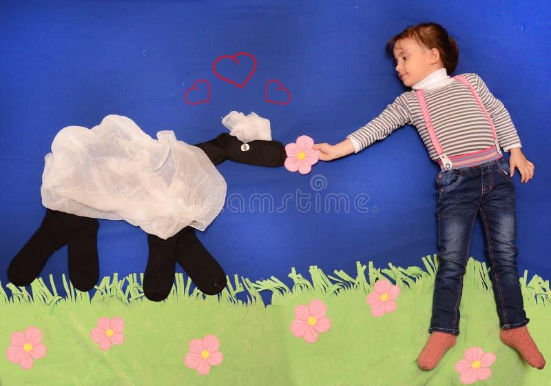 Kind, das ein Lamm spielt und einzieht lizenzfreies stockfoto