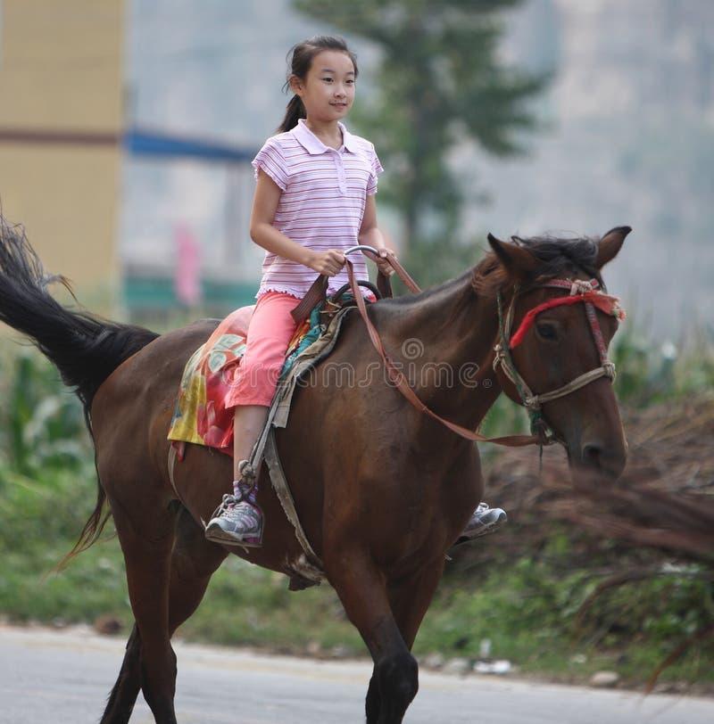 Kind, das ein Pferd reitet lizenzfreie stockfotografie