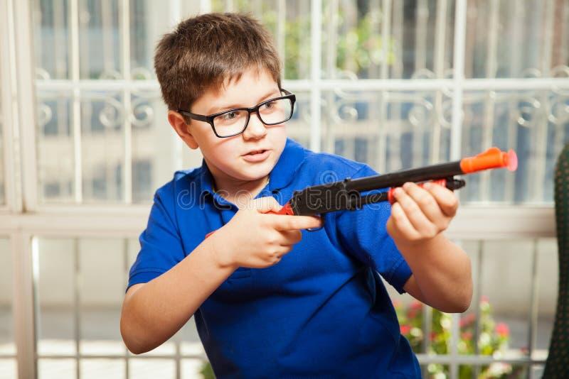 Kind, das ein Spielzeuggewehr schießt stockfoto