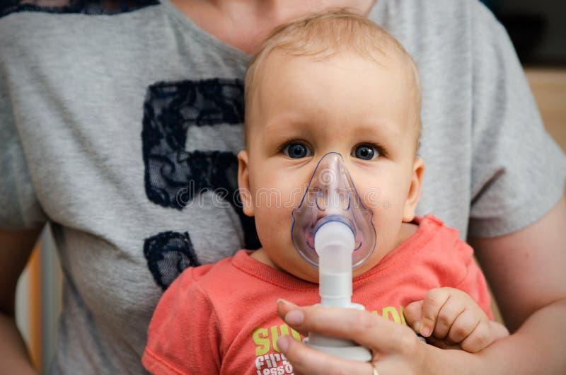 Kind, das Einatmung mit Maske auf seinem Gesicht macht stockfotografie