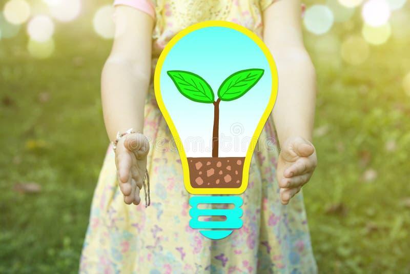 Kind, das eine Birne mit einem Betriebswachsenden Innere als ` grünes denkendes ` Konzept an einem sonnigen Tag hält lizenzfreies stockbild
