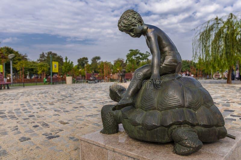 Kind, das eine enorme Schildkröte reitet lizenzfreies stockfoto